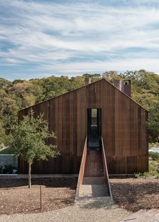 In order to leave the hills intact, the builders excavated uphill and added a steel-grated bridge to connect the upper sleeping level to the hillside and the adjacent tack barn.