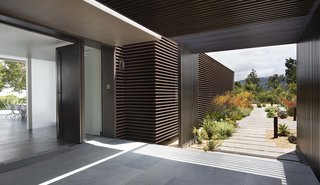 """""""When you pull up to the garage doors, you intuitively know where the front door is, but there's nothing that says entrance,"""" he says. """"Instead we did it through the landscaping and architecture."""""""