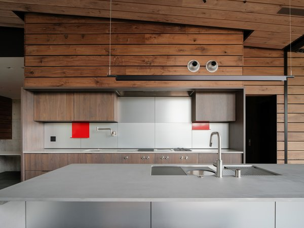 The streamlined Henrybuilt kitchen features a hidden range hood and pops of color that reference the home's red-tinted glass.
