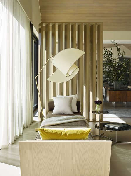 This cozy lounge area captures golden hour sunlight. It features a custom-designed daybed and a Carlo Mollino floor lamp.