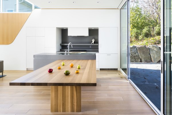 The double-duty kitchen island is a simple offshoot that contrasts with the industrial countertops.