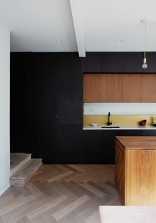 Dumas kept a relatively simple palette when it came to the interior. Floor-to-ceiling cabinetry in the kitchen acts as an effective noise barrier.