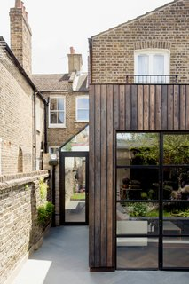 Charred Siberian timber complements the original brick home.