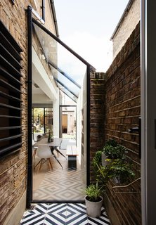 Trellik Design Studio opened up the alleyway to provide an indoor/outdoor corridor, which livens up the dated home and provides more outdoor space.