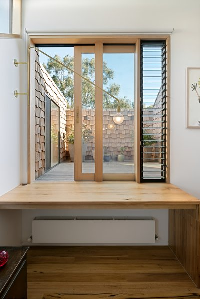 "The study at the top of the stairs allows access to the first-floor deck, and it's one of the most unique design features in the home. ""The raw brass swinging arm light can be rotated off the wall and positioned as required when sitting at the desk, while the light can be swung against the wall when accessing the deck,"" Rhodes says."