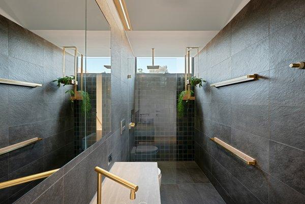 Custom brass plant shelves and custom tile adorns the master bathroom.