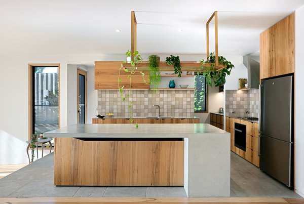 Recycled veneer coats the cabinetry, custom plant holders bring the outside in, and stainless steel provides a modern touch without seeming stark.