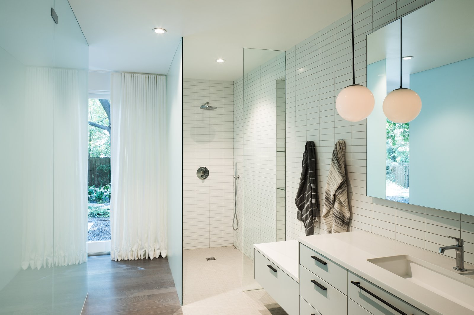Toyath Residence by Webber + Studio all-white bathroom with glass-enclosed, walk-in shower