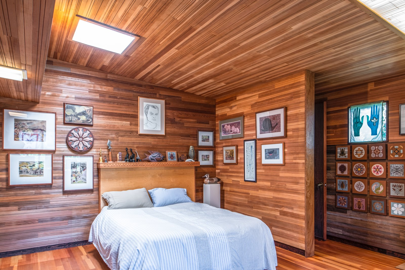 Bedroom, Bed, Storage, Night Stands, Light Hardwood Floor, and Ceiling Lighting Locally milled wood clads the interior of this massive artist's compound.   Photo 5 of 10 in Renowned Artist Emile Norman's Sensational Big Sur Home Lists for $2M