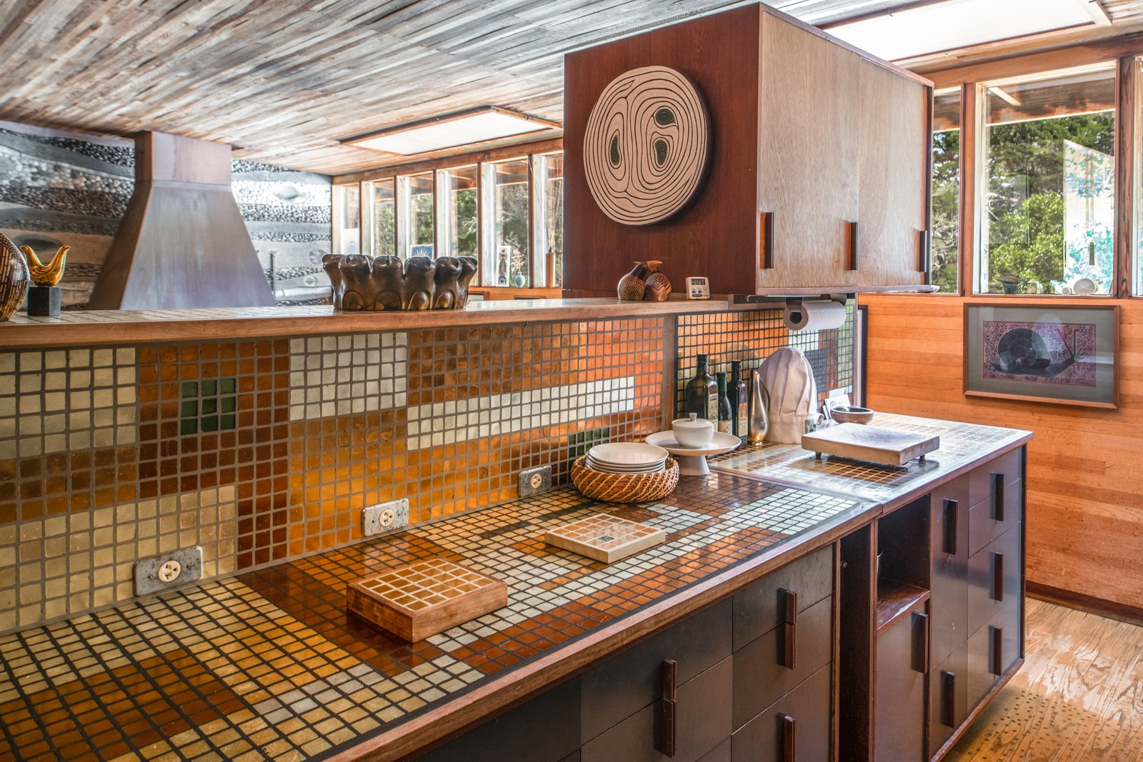Kitchen, Tile Counter, Cooktops, Wall Oven, Medium Hardwood Floor, Wood Cabinet, Glass Tile Backsplashe, and Refrigerator The kitchen features a 24-karat gold cooktop and rose gold tile.  Photo 7 of 10 in Renowned Artist Emile Norman's Sensational Big Sur Home Lists for $2M