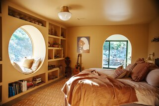 The circular window seat was inspired by Thomas's love for Los Angeles's Spanish Colonial homes, while the built-in shelves were taken from a look Studio Shamshiri did for  Sonia Boyajian Jewelry in L.A. Clay pieces Thomas found on her travels to Oaxaca fit nicely with the irregular shape of the shelving.