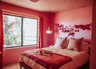 Textiles from St. Frank accent the all-pink guest room.