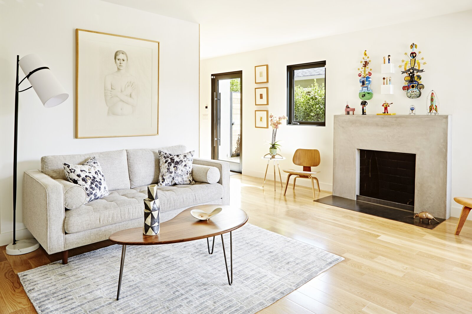 Living Room, Chair, Light Hardwood Floor, Sofa, Standard Layout Fireplace, End Tables, Ceiling Lighting, Coffee Tables, and Floor Lighting The now cozy entryway features a mismatch of the couple's collection.  Photo 2 of 8 in Budget Breakdown: This Sunny 1939 Santa Monica Bungalow Shines After a $765K Remodel