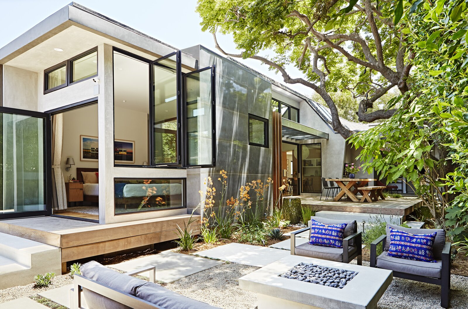 Outdoor, Walkways, Hardscapes, Back Yard, Trees, Grass, Shrubs, Gardens, and Large Patio, Porch, Deck The large Chinese Flame tree can be fully enjoyed from the two outdoor seating areas.  Photo 5 of 8 in Budget Breakdown: This Sunny 1939 Santa Monica Bungalow Shines After a $765K Remodel