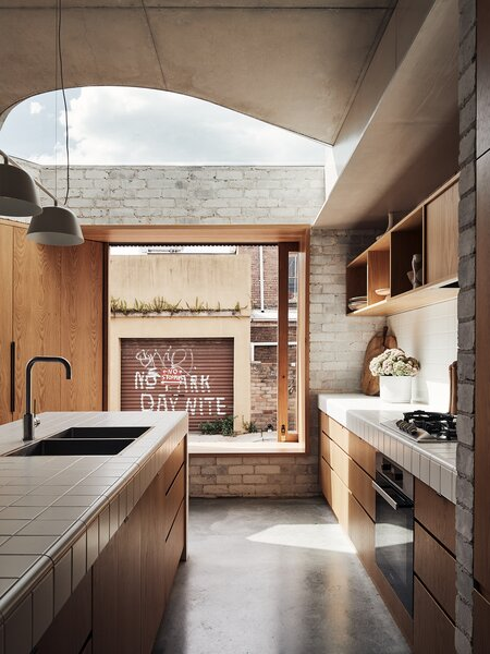 Plaster and tile play nicely with brick and steel in this Bondi beach home defined by sharp contrast.
