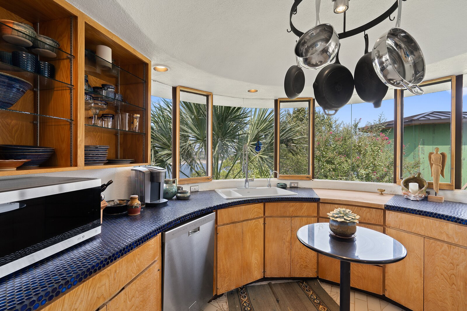 Glass tiling can be seen in the rounded kitchen.  Photo 4 of 7 in Austin's Weird and Wonderful Sand Dollar House Can Be Yours for $2.2M Clams