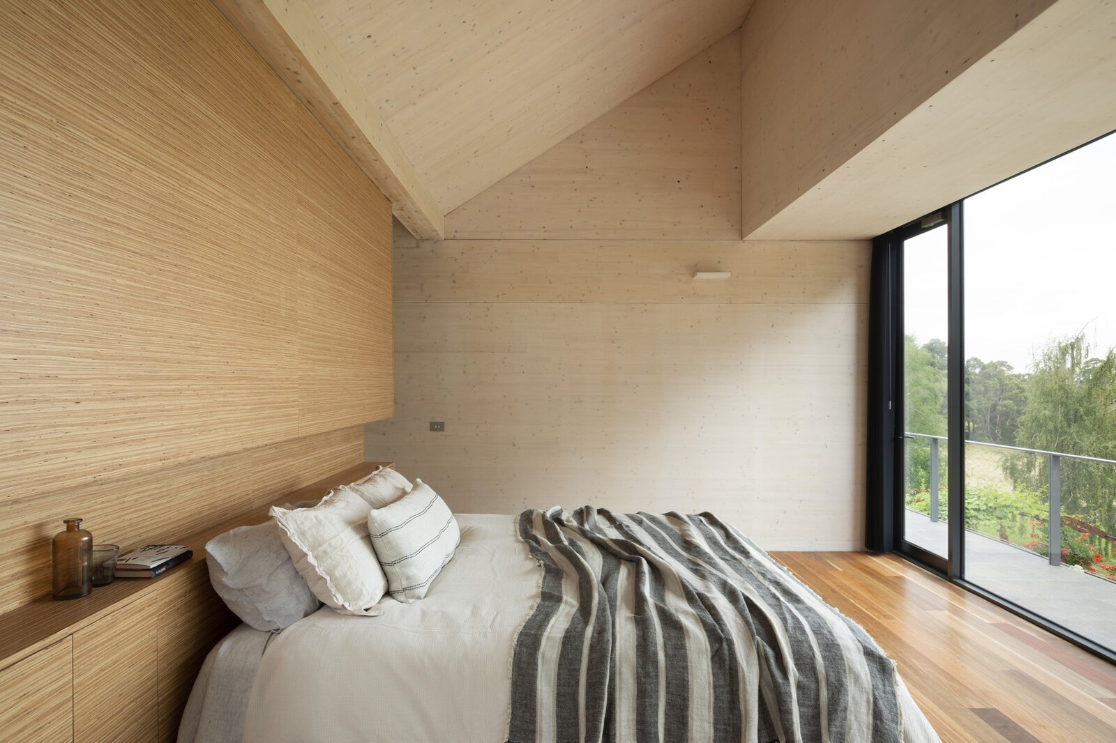 Bedroom, Bed, Storage, Ceiling Lighting, and Medium Hardwood Floor The simple interiors complement the usage of CLT throughout.  Photo 4 of 7 in Cross-Laminated Timber Gives This Renovated 1970s Australian Farmhouse a Bold Look