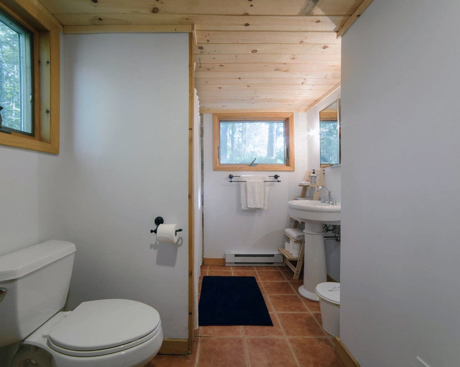 Bath Room, Ceramic Tile Floor, Pedestal Sink, Ceiling Lighting, Two Piece Toilet, and Enclosed Shower Before: The drab first-floor bathroom needed to be opened up and now borrows space from an adjacent closet.  Photo 12 of 16 in Before & After: A Creative Couple Revive a 1950s Cabin in the Catskills