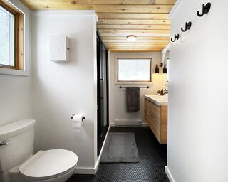 """The bathroom has amazing daylight, which we found to be rare,"" says Lauren. They added a full vanity to better service guests, rebuilt the walk-in shower, and added a laundry area and additional storage. Black penny tile flooring echoes black hardware."