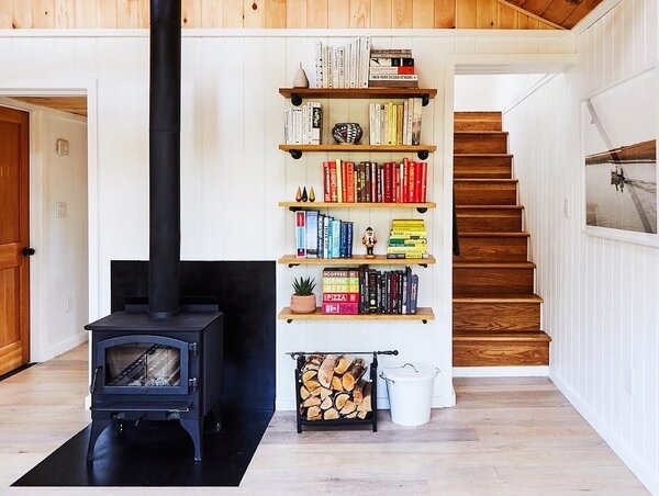 The team leveled the floors and brought the stairs up to code. A NextGen-Fyre wood stove by Lopi feels much more appropriate for the room's proportions.