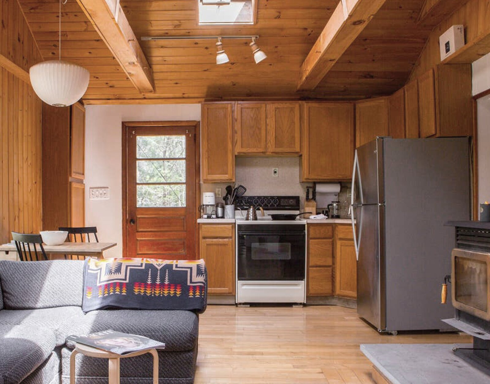 """Kitchen, Refrigerator, Wall Oven, Microwave, Cooktops, Light Hardwood Floor, Wood Cabinet, and Dishwasher Before: The kitchen felt cramped with clunky appliances and lots of wood. """"It was really overwhelming,"""" says Lauren.  Photo 7 of 16 in Before & After: A Creative Couple Revive a 1950s Cabin in the Catskills"""