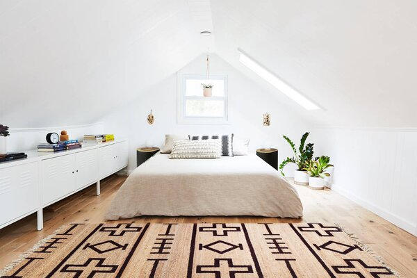 """The second bedroom peaks at seven feet, so even adults can stand straight up in the lofted room. """"It's been really fun for our friends that have kids because they can have their own space,"""" says Lauren. It also doubles as a studio and workspace."""