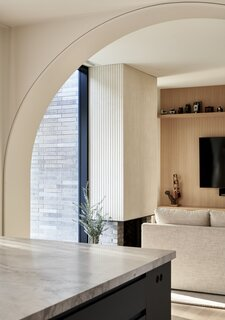 The curvature keeps the home cozy as it breaks up the open-concept main spaces. In the family room, there is a fluted concrete fireplace.