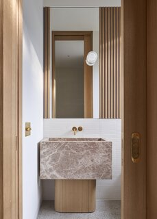 The powder bathroom features a custom stone sink and white oak vanity base built by the homeowner.