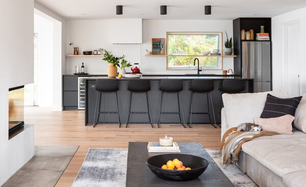 """The main goal for the living room was to double the size. """"The clients talked about it being the space where everyone congregated, where the adults could have conversations and kids could play without being on top of one another,"""" says Fong. The tranquil hub is connected to the kitchen and dining room and visually separated via a three-sided fireplace."""