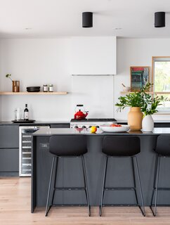 The kitchen, kept in the same location, was opened up dramatically. Gray cabinets from IKEA are topped with honed granite countertops; an oil painting of the original cottage sits on one of the floating shelves.