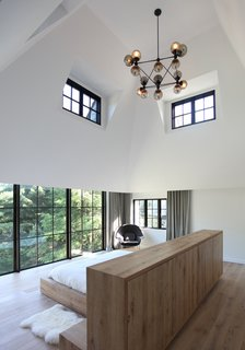 The high-ceilinged master bedroom of Sterling Ridge enjoys unobstructed views of the surrounding forest.