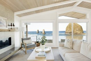Melanie Gaither Interiors selected light, beachy furnishing and finishes to match the view outside Haystack Rock Getaway. A deck outside the living room extends the connection to the ocean.