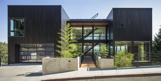 The U-shaped plan of Music Box Residence by Scott Edwards Architecture has large volumes on both sides with a glassy two-story entry space in the middle. A long bridge, with a bamboo forest below, leads from the sidewalk to the main entry. The exterior is clad in black stained siding reminiscent of sho-sugi ban in order to pay homage to the family's Japanese ancestry.