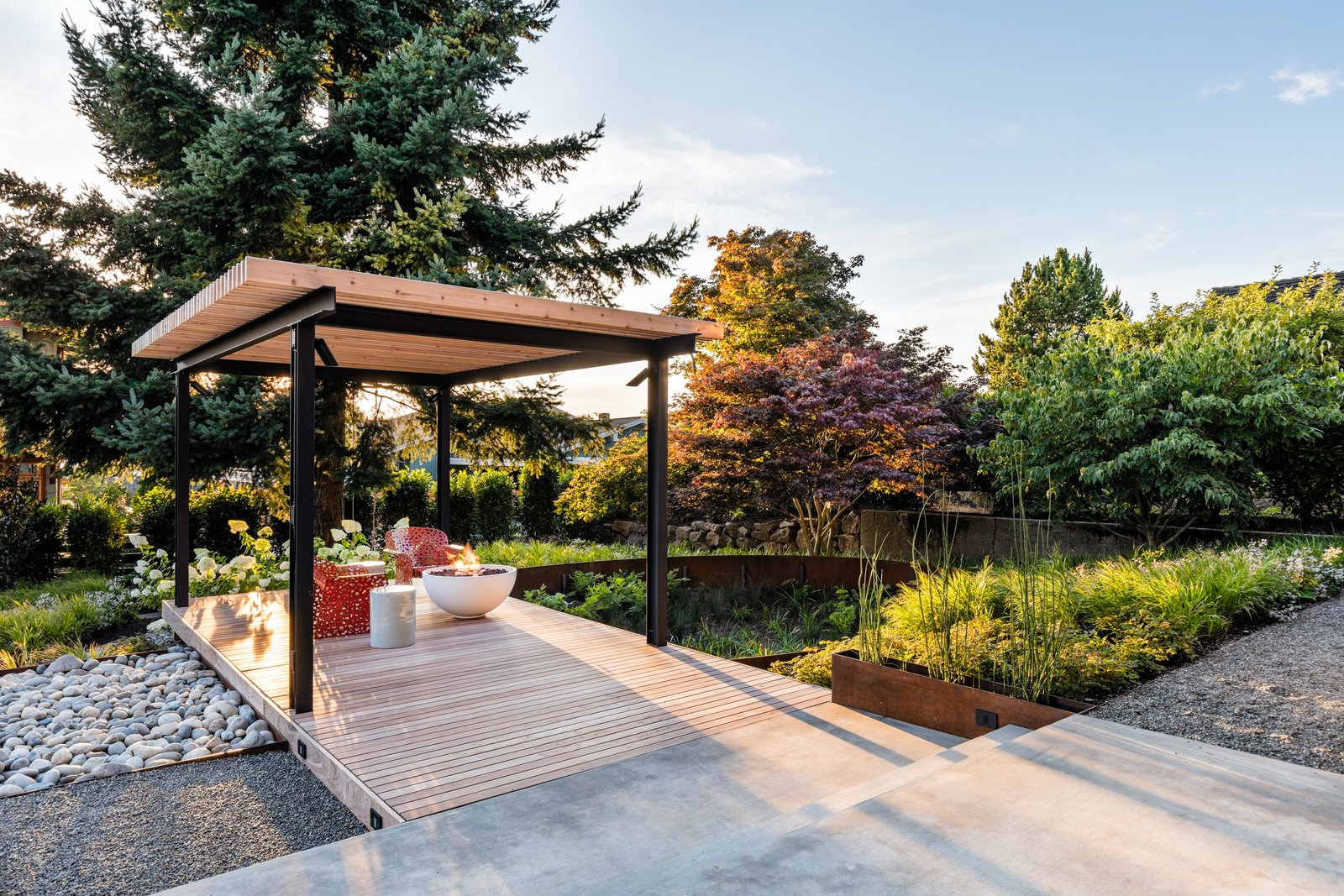 Outdoor, Back Yard, Wood Patio, Porch, Deck, and Gardens An arbor-covered deck looks out over an oval rain garden planted with a mix of flowering native plants.    Magnolia Modern by Land Morphology