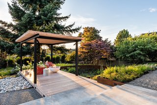 An arbor-covered deck looks out over an oval rain garden planted with a mix of flowering native plants.