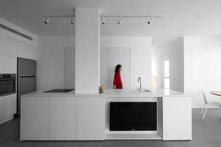 The kitchen replaced a former hallway with custom-designed MDF cabinetry and an island topped with quartz.