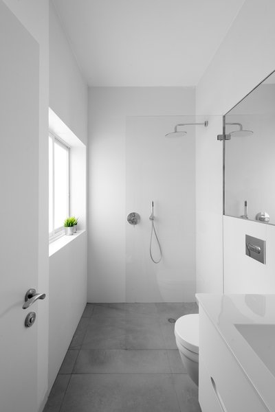 The en suite master bath slips behind the kitchen, and features gray ceramic tiled floors used throughout the apartment.