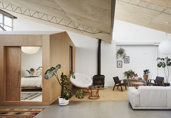 The wood-burning fireplace in the living room is vented through the warehouse's sawtooth roof, sheathed in plywood above the living room.