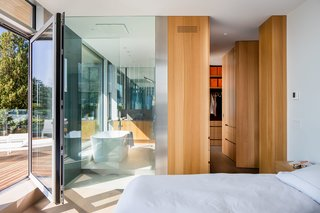 The master bedroom features a white oak walk-in closet and an en suite glass-walled bathroom with a soaking tub and a glass-enclosed shower.
