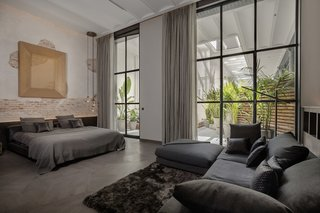 The parquet floor in the master bedroom is stained gray and cut in irregular polygonal shapes.