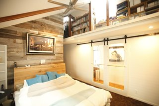 Reclaimed wood and lofted shelving trims the master bedroom.