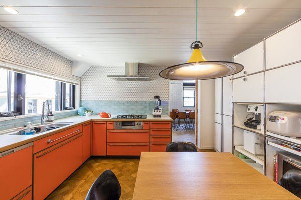 The orange custom cabinets in the kitchen were specially manufactured by Factory Tool.
