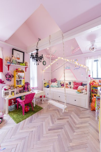 Herringbone floors and pink walls brighten the girl's bedroom.