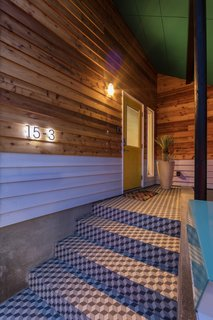 Geometric tiles cover the existing front steps in the covered parking spot.