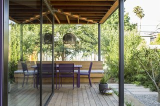 A cedar deck, built-in bench, and Fermob Costa table and chairs under a new porch roof serve as a year-round dining area.