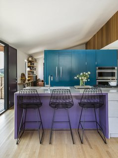 The coved roof and arched doorway came out, and the teal cabinets create a separation between the kitchen and living room.