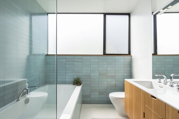 The main bathroom features a soaking tub, Hansgrohe faucets, and bathroom tiles from Heath Ceramics and American Universal Penny.