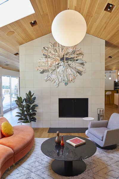 The ceramic piece over the two-sided fireplace is by Brie Ruias, with Jasper Morrison Glow Ball light above.