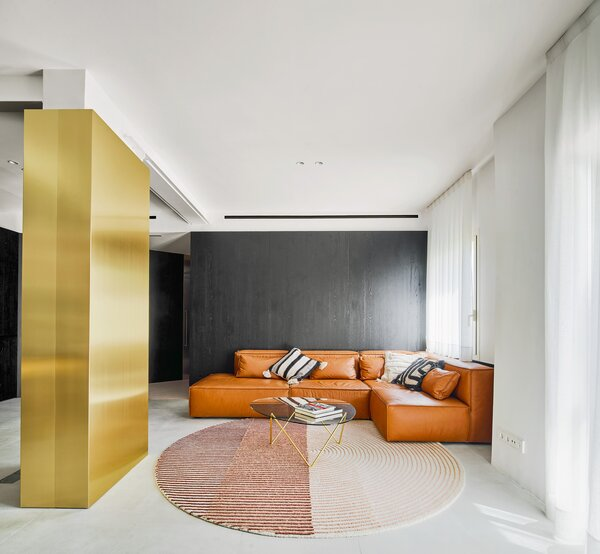 Materials like the tan leather sofa and circular area rug soften the stark contrasts in color.