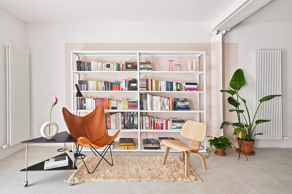 A light pink accent wall behind the bookshelf ties the library area with the triangular threshold to the bedrooms.